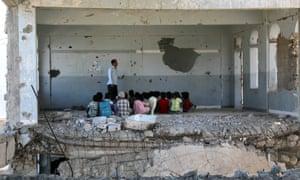 Los niños yemeníes asisten a una clase en una escuela dañada por una bomba en Taez el primer día del nuevo año escolar, el 3 de septiembre.