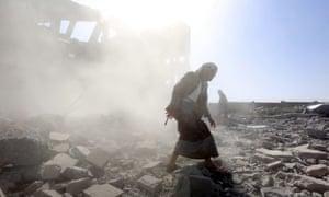 Hombres armados inspeccionan un centro de detención retenido por Houthi después de que fue golpeado por presuntos ataques aéreos controlados por Arabia Saudita en Dhamar, Yemen, el 1 de septiembre de 2019.