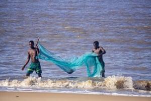 José Fernando y un amigo regresan de un viaje de pesca en la ciudad costera de Beira en Mozambique
